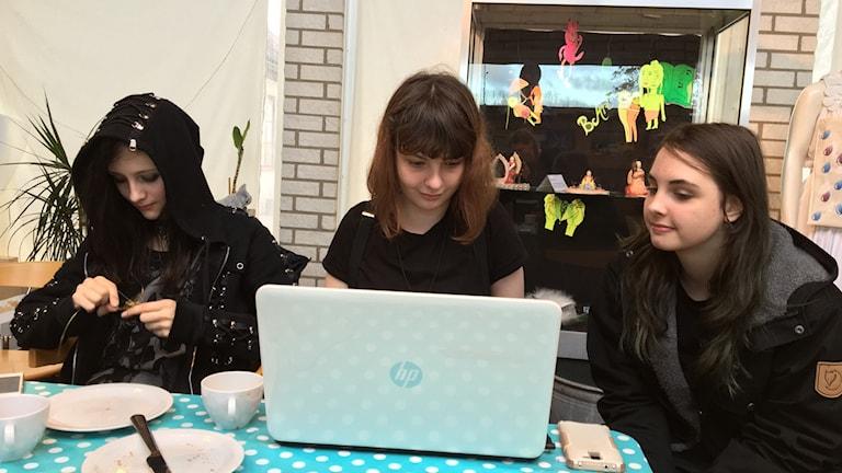 Katarina, Lina och Emma sitter vid ett bord och två kollar på en datorskärm. Katarina arbetar med metalltråd.