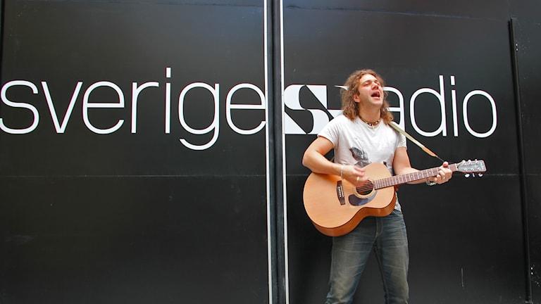 Musikern Simon Andersson, utomhus, spelar gitarr och sjunger. Foto: Mette Mjöberg Tegnander/ Sveriges Radio