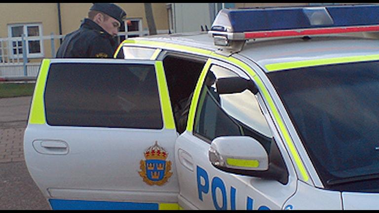 Polis vid polisbil. Foto: Polisen