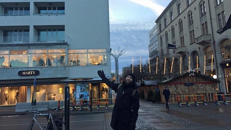 Olle Toftenow visar den tomma väggen på Gustav Adolfs torg där den strömmade livesändningen av de sovande björnarna visas när det är mörkt på Gustav Adolfs torg i Malmö. Foto: Rafaela Stålbalk Klose/Sveriges Radio