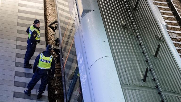 Poliser på väg att utföra gränskontroll i tåg på Hyllie station. Foto: Johan Nilsson/TT.