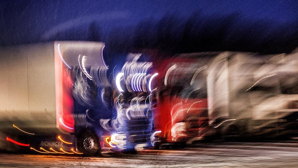 Lastbilar i mörker, fladdrigt ljus.