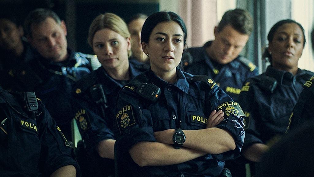 grupp personer i polisuniform. kvinna med armarna i kors står längst fram