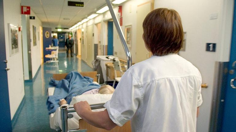 Sköterska rullar säng genom sjukhuskorridor. Foto: Erik G Svensson/TT.