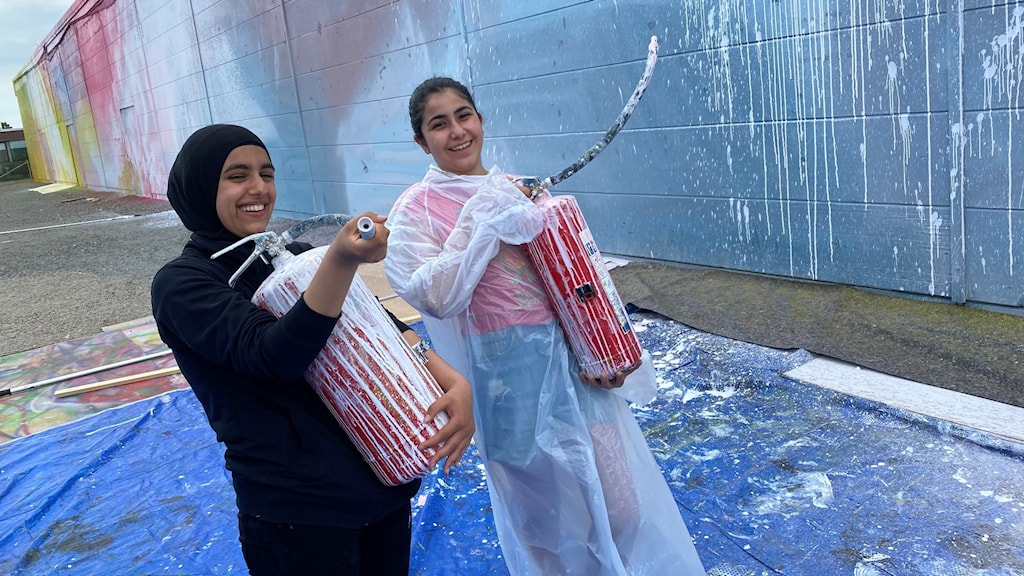 Två flickor med skyddskläder framför en stor ljusblå vägg.