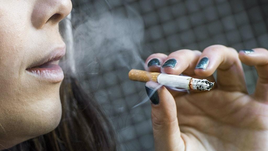 Bilden visar munnen och handen på en ung kvinna som röker. Foto: Claudio Bresciani/TT.