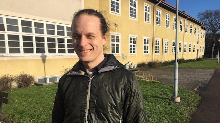 Ludvig Haav projekt ledare står framför ett gult hus som är en gammal sjukhuspaviljong. han tittar in i kameran och skrattar.