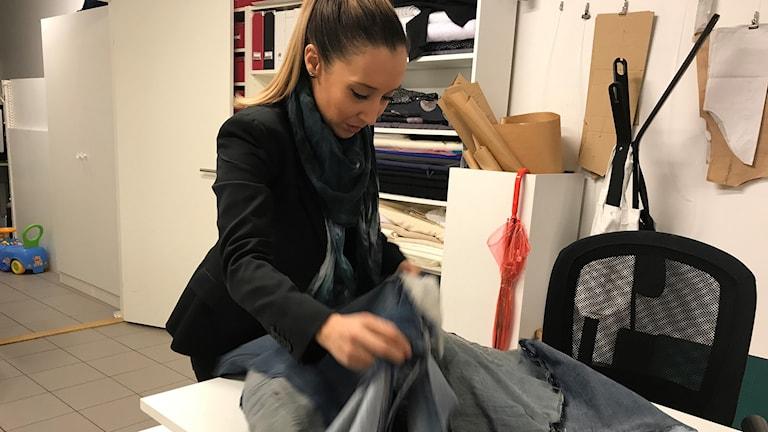 Kvinna i svart kavaj och blå scarf hanterar jeanstyg.