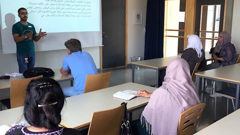 Man undervisar elever i samhällsorientering i ett klassrum.
