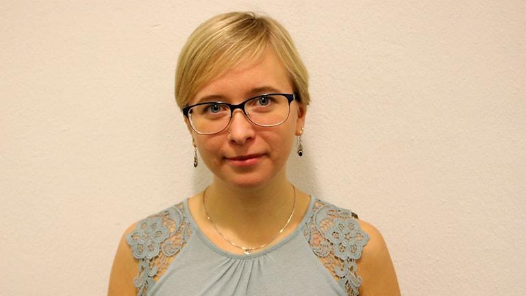 Sophie Oppong har psoriasis, står framför en vit vägg.