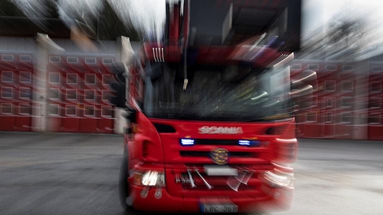 Suddig bild av brandbil på utryckning.