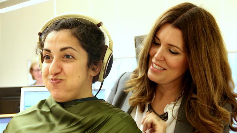 Nadia blåser upp kinderna i en grön sjal.