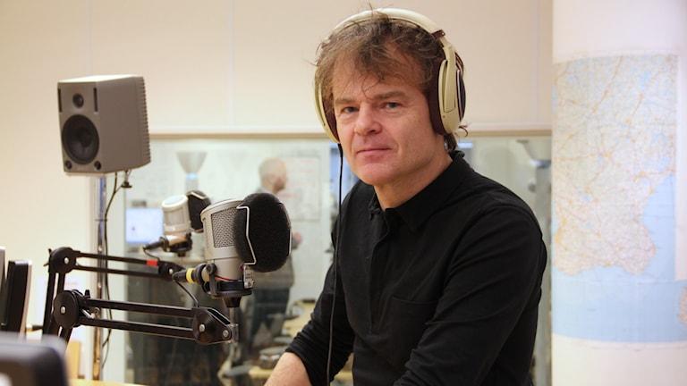 Nisse Hellberg står i studion på P4 Malmöhus. Han har stora hörlurar på sig och en svart tröja.