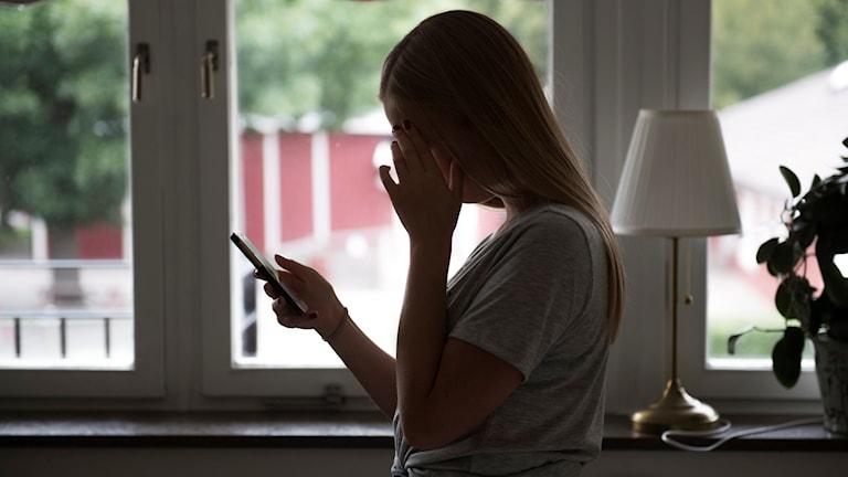 Flicka tittar i mobiltelefon. Foto: Fredrik Sandberg/TT.