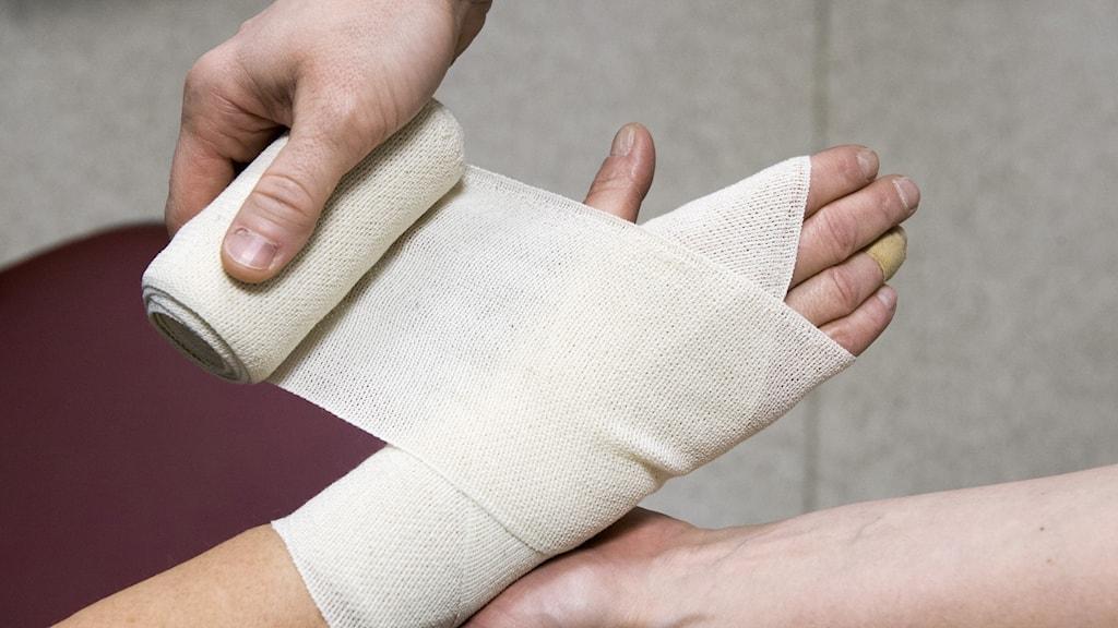 Sjuksköterska lägger bandage på patient.