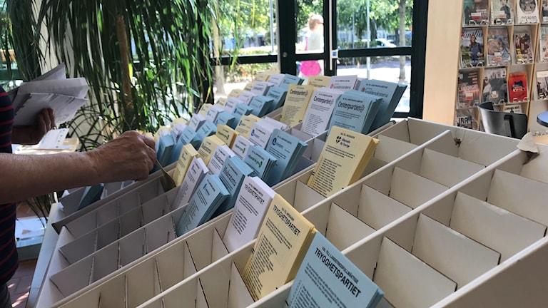 En person plockar på sig valsedlar inför förtidsröstningen.