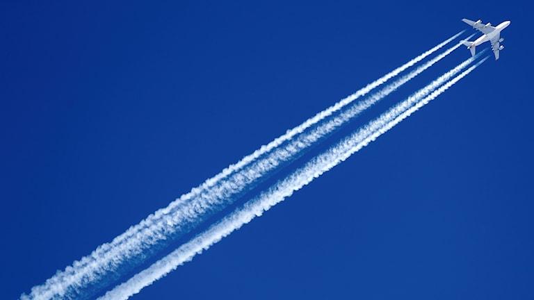 Flygplan med avgaser på blå himmel.