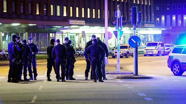Poliser i förgrunden på platsen där en polisbil sprängdes.