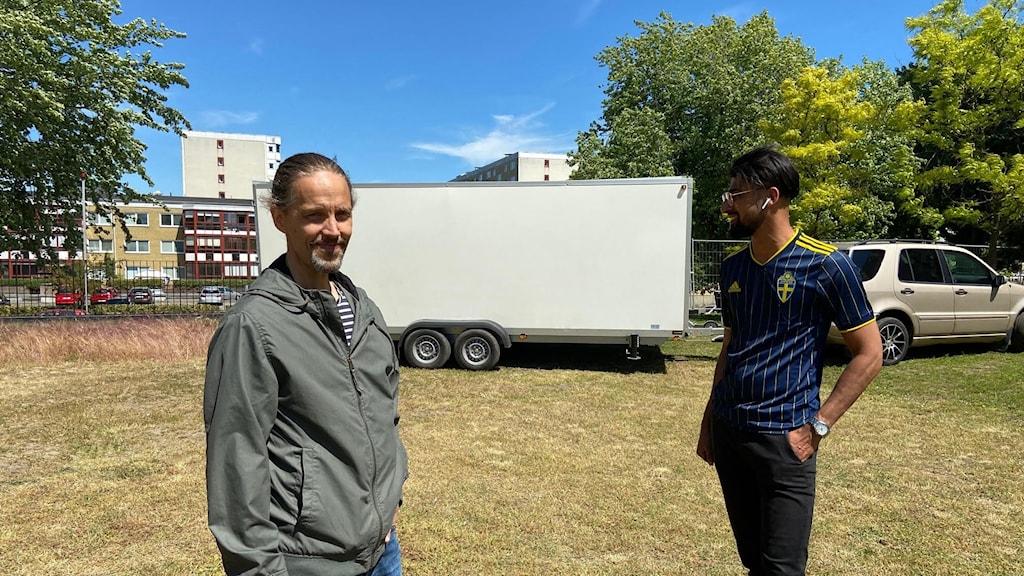 Två män står framför en storbildsskärm