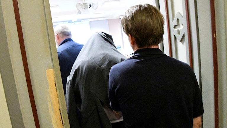 Bild på misstänkt på väg in i rättssalen
