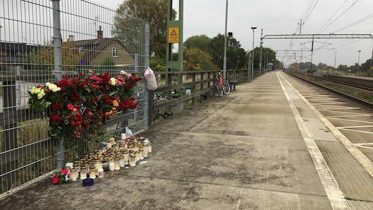 Folk har lagt blommor och tänt ljus på den plats där en man i 20-årsåldern dog när han träffades av tåget vid stationen i Åkarp. Foto: Anja Bergdahl/Sveriges Radio