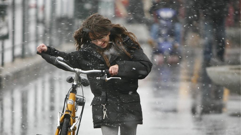 Kvinna med cykel i snöväder.