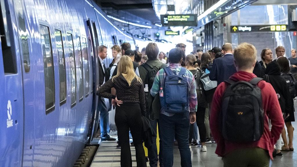 Människor på väg in i pågatåg vid Malmö centralstation