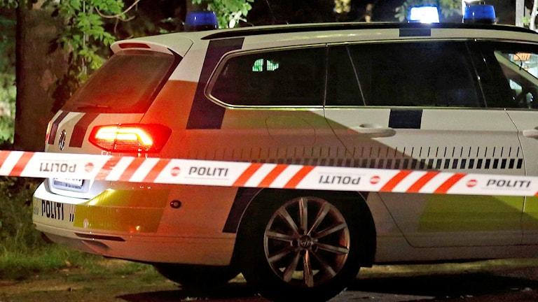 En dansk polisbil bakom en polisavspärrning.