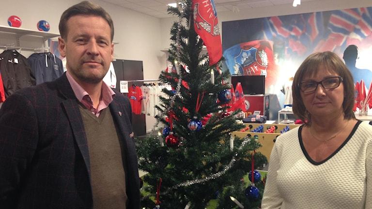 Klubbdiretör Mats-Ola Schulze och försäljningschef Helena Wennerström står på varsin sida om en pyntad julgran med en Helsingborgs IF-flagga i topp.