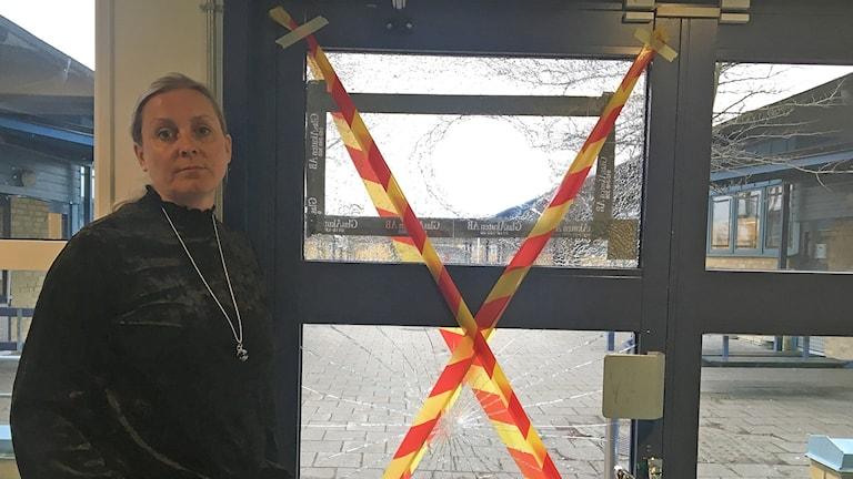 Dalhemsskolans biträdande rektor Nina Pringle vid en av de många krossade rutorna. Foto: Nina Sköldqvist/Sveriges Radio.