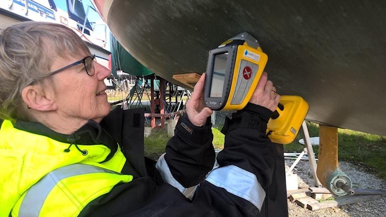 Britta Eklund mäter båtbottenfärg i Limhamn, med en metod som baseras på röntgenflourescens.