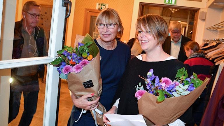 Socialdemokraterna Katrin Stjernfeldt Jammeh och Carina Nilsson med blommor i händerna.