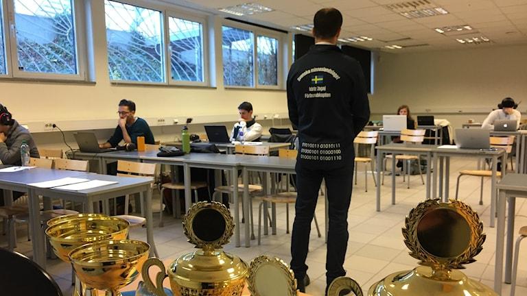 Bilden visar tävlande i EM i Minne. De sitter i ett klassrum på Svaneskolan i Lund. Domaren Idriz Zogaj står upp och håller koll. I förgrunden prisbordet med pokaler. Foto: Anna Bubenko/Sveriges Radio.