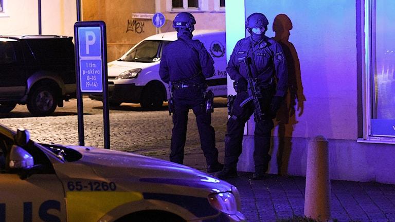 Två poliser står i ett gathörn med vapen.
