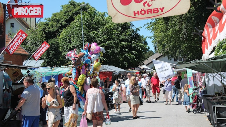 På bilden syns en folkmassa som går längs med en gata en sommardag. Ut med sidorna är små affärststånd uppställda.