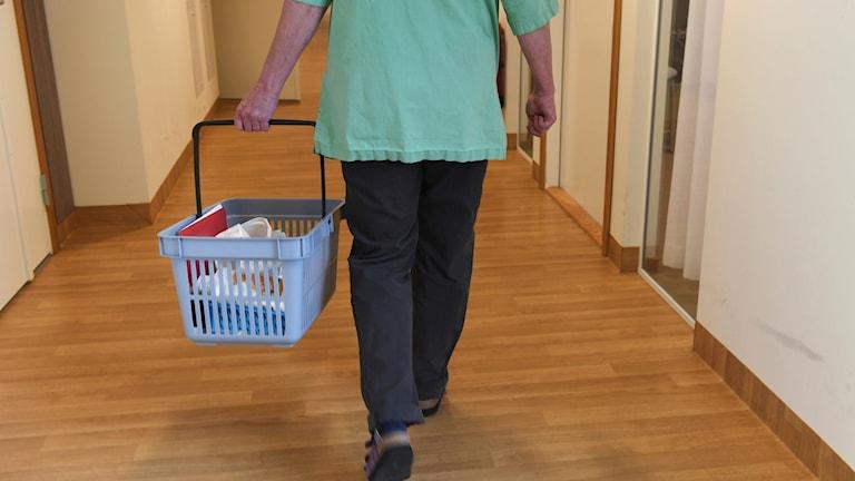 Personal på ett demensboende går genom en korridor för att ge de boende sin medicin.