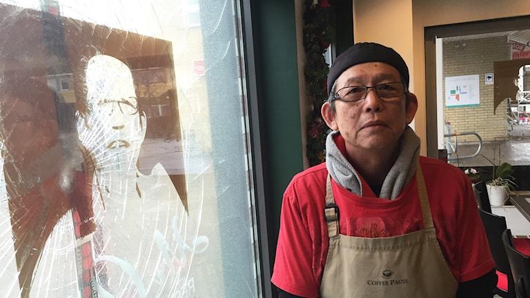 Restaurangägaren Joakim Chow står vid ett trasigt fönster.