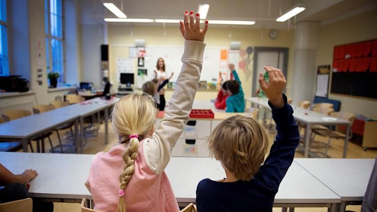 två barn räcker upp handen för att svara på en fråga i klassrum