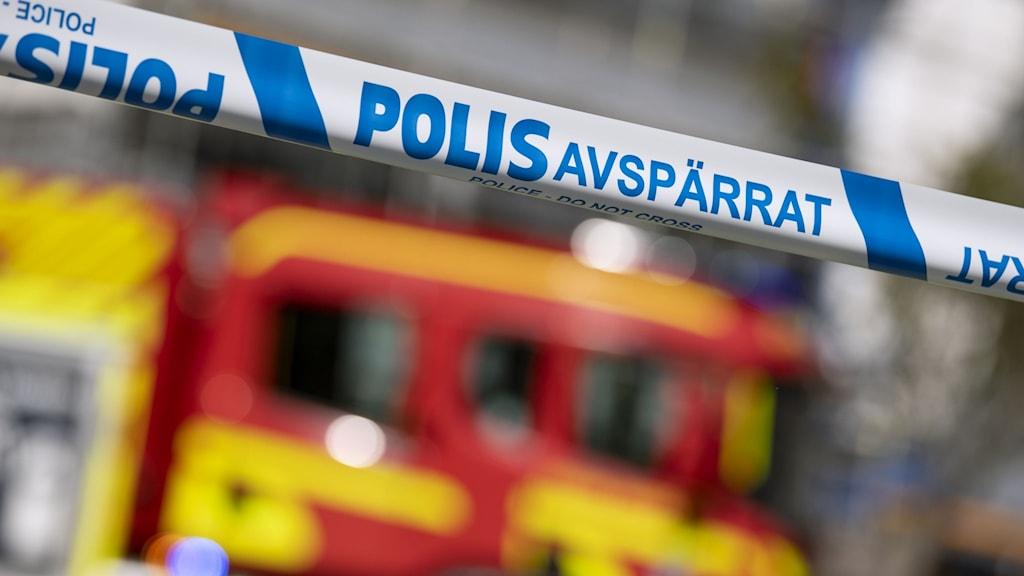 På bilden ser man ett blåvitt avspärrningsband från polisen, bakom bandet skymtar konturerna av en röd brandbil. Foto: