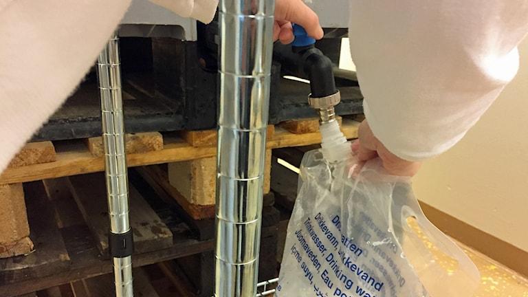 Sjukhusets personal i Lund fyller på vatten ur stora dunkar för att klara verksamheten. Foto: Victor Pandurescu/Sveriges Radio.