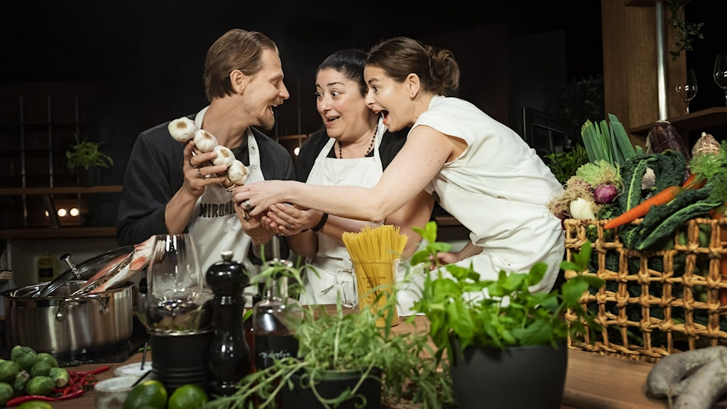 Tre personer som håller i en fläta av vitlök i ett kök