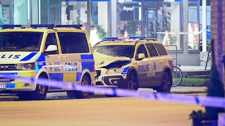 Två polisbilar, den ena med trasig motorhuv.