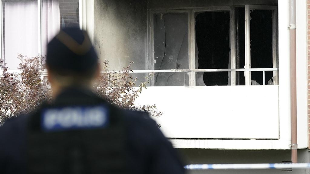 Polisrygg i förgrunden och en balkong på ett hyreshus med sot och krossade rutor