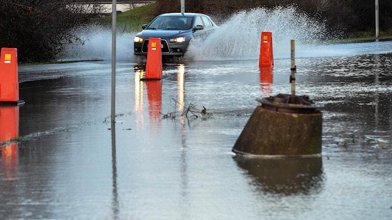En bil kör i vatten på en väg.
