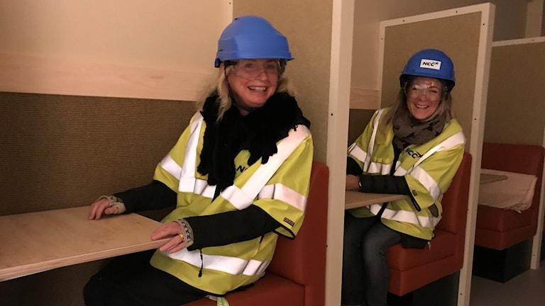 Med blåa bygghjälmar och reflexvästar sitter rektor och skoladminsitratör i kupéliknande bås i nya Brogårdaskolan i Bjuv.