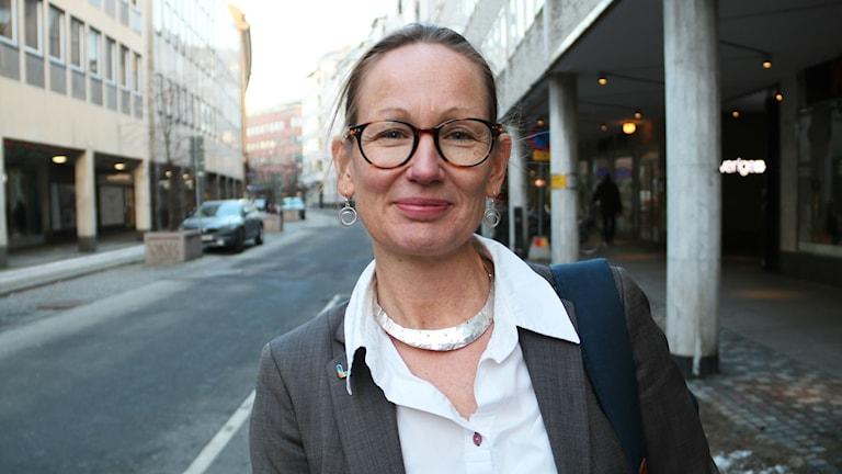 En kvinna med glasögon, grå kaval och vit skjorta tittar rakt in i kameran i stadsmiljö.