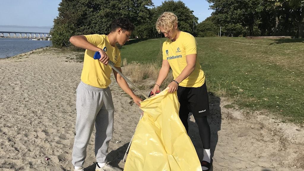 Daniel Naguib och Hugo Svensson från FC Rosengårds Futsallag städar bort skräp från Sibbarpsstranden i Malmö