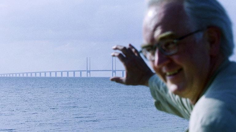 Christoffer Barnekow med Öresundsbron i fonden. Håller en av pylonerna mellan tumme och pekfinger.
