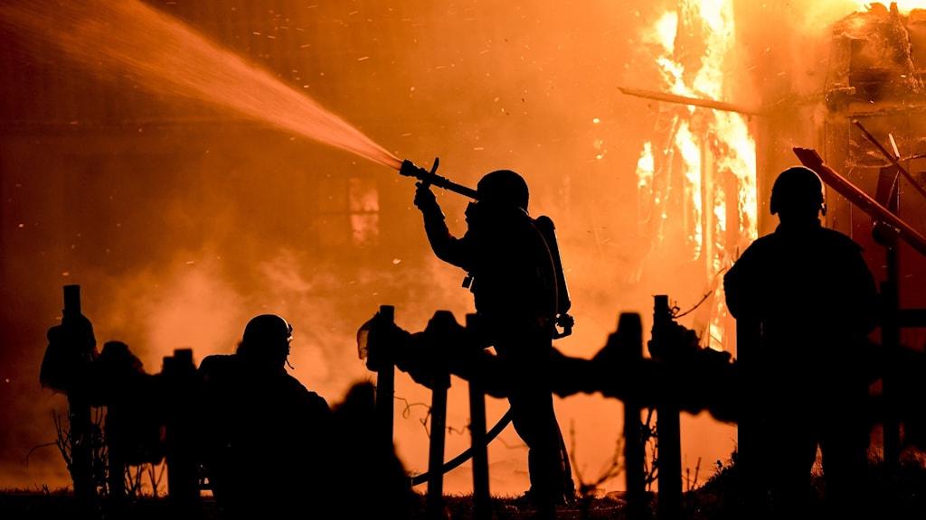 Eldhav i natten, räddningspersonal som skuggor i förgrunden.