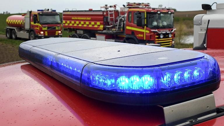 Räddningstjänstens fordon bakom ett blåljus.